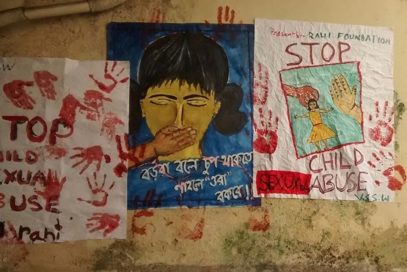 "The photograph shows a series of posters developed by students of Vidyasagar School of Social Work, Kolkata as part of a child sexual abuse awareness generation workshop organized by RAHI Foundation in 2015. There are three posters pasted on a wall next to each other with messages related to child sexual abuse in English and Bengali. One of them says, ""Stop child sexual abuse"" with imprints of human hands all around the text – both text and imprints are in red colour. Another poster adjacent to the first shows a large and beautifully drawn illustration of the face of a girl child with her eyes closed and a hand placed on her mouth to stop her from speaking. The text below the illustration, when translated from Bengali into English, implies that the elders say children should keep quiet about sexual abuse, or else the 'abusers' will scold them. The third poster shows the illustration of a small girl child with her hands spread out, and the hand of a grown up, much larger in size than the child, next to her. The entire illustration is enclosed inside a square box. The text above and below the box says in capital letters ""Stop child sexual abuse"". This poster too has imprints of the human hand in red colour spread around the box. The names of RAHI Foundation and Vidyasagar School of Social Work are mentioned on the edges of the posters. Photo courtesy: RAHI Foundation"