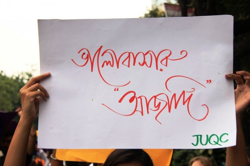 "This photograph shows a poster held up by a participant at a rally in Kolkata on September 16, 2018 to celebrate the Supreme Court's verdict reading down Section 377 of the Indian Penal Code. The poster, prepared by the Jadavpur University Queer Collective, simply says ""Bhalobashar aajadi"" in Bengali, which translates as 'freedom to love'. The text is written in big bold letters in red on a white chart paper. The initials JUQC are mentioned on the bottom right corner. The poster fills up the main part of the photograph, with only the hands and a part of the participant's head visible on the edges of the poster. In the background more participants can be seen. Photo credit: Kaushik Gupta"