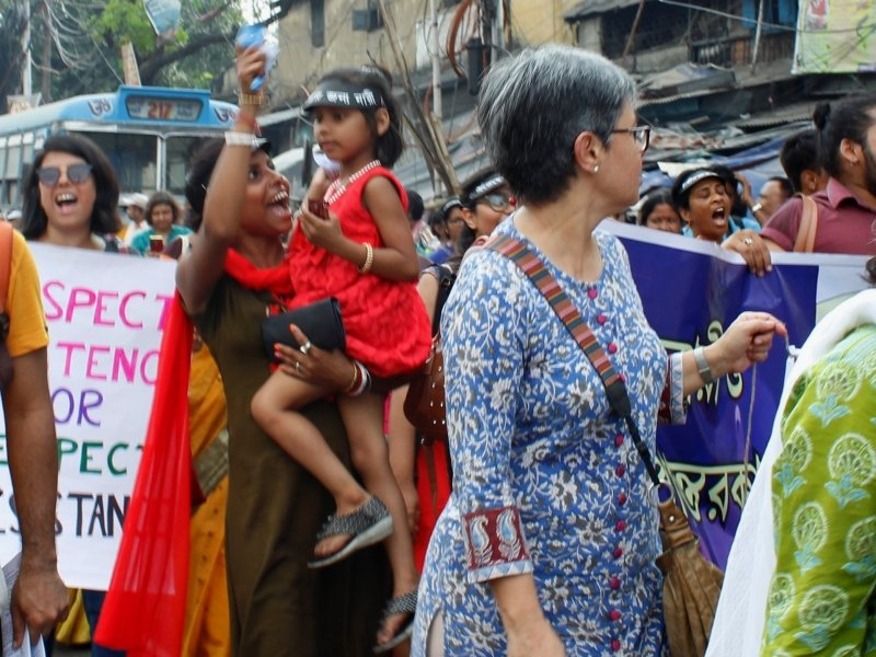 This photograph contrasts with the previous one – in terms of the age profile of the participants at the 'Kolkata Women's March'. It shows a young woman holding a girl child in her left arm, while her right hand is raised high as she cheers and shouts out a slogan. The child, wearing an eye shade cap, looks on with fascination and seems to be holding on to a small chocolate in her left hand. There is a crowd of other participants in the march around this pair, carrying banners and shouting slogans. The backdrop shows a part of a public bus (with route number 217 displayed in a panel above the bus windscreen), an old building and some hawker stalls on the roadside. Photo credit: Rith Das