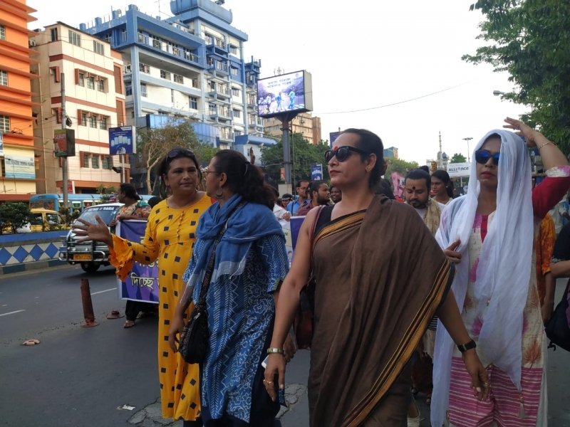 This photograph shows some of the key organizers of the 'Kolkata Women's March' on April 4, 2019. Most of the individuals in this group of walkers are trans persons. Trans women's groups played a leading role in organizing the march. Some of the individuals in the picture are talking to each other; behind them are other walkers carrying banners and posters. The backdrop shows road traffic, buildings, trees, hoardings and a cloudless summer sky. Photo credit: Rith Das