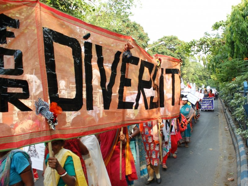 This is a long shot of an elongated banner titled 'For Diversity' being held up by the walkers at the 'Kolkata Women's March' with sticks in their left hand. The banner therefore is facing the pavement to the left of the walkers – to provide a prominent view to the pedestrians. The banner text is in large bold lettering. The photograph backdrop shows the procession extending way beyond the walkers holding up the banner mentioned. It also shows considerable greenery – trees and other foliage – on either side of the road being used by the walkers, and a glaring summer sky. Photo credit: Rith Das