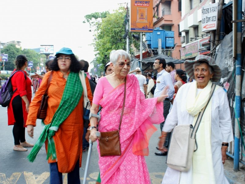The focus in this photograph is on three elderly women participating in the 'Kolkata Women's March' held on April 4, 2019. One of them seems to be in her 50s, while the other two are likely to be in their late 60s or 70s. The women are smiling and seem to be enjoying themselves. One of them is using a walking stick; two of them are wearing caps to protect themselves from the sun. In the backdrop are more walkers, buildings to the left of the walkers, the usual clutter of street furniture on Kolkata pavements, some trees, hoardings and a partial view of the sky. Photo credit: Rith Das