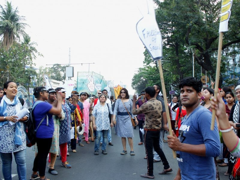 "This final photograph was taken somewhere towards the end point of the 'Kolkata Women's March'. Around 25 individuals (mostly women and some men) can be seen in the photograph standing in a semi-circle. They are carrying posters and cut-outs; some are clapping, while others are shouting out slogans. Many are in smiles; a few can be seen taking photographs using their mobile phones. One of the cut-outs in the foreground is a human fist with the forefinger stretched out – it has text that says ""Freedom of speech"". The background is dominated by a hazy summer sky, a lamp post with a hoarding, some buildings barely visible in the distance, and trees lining either side of the road. Photo credit: Rith Das"