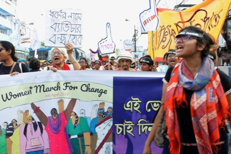 "This photograph shows an upfront shot of the 'Kolkata Women's March' held on April 4, 2019 – scores of women can be seen marching behind the main banner, shouting out slogans. The banner is titled 'Women* March for Change – 4th April 2019' and a graphic below the title shows several women participating in a protest with raised fists. The artwork style is such as to show the women possessing immense strength. The women are all dressed differently, and one of them is using a walking stick. The women outside the banner, that is, those actually participating in the march are similarly from different age groups and socio-economic backgrounds. One young woman is walking ahead of the main banner (to the right of the photograph), partially blocking the view of the banner. The participants are holding up posters and cut-outs. One of the posters, when translated from Bengali, says 'stop intolerance and violence in the name of religion'. Most of the cut-outs show human fists with the forefinger stretched out and marked with the voting ink. The cut-outs also have single word texts like ""Ganatantra"" and ""Democracy"". Buildings, public buses, lamp posts and a glaring summer sky form the photograph backdrop. Photo credit: Rith Das"