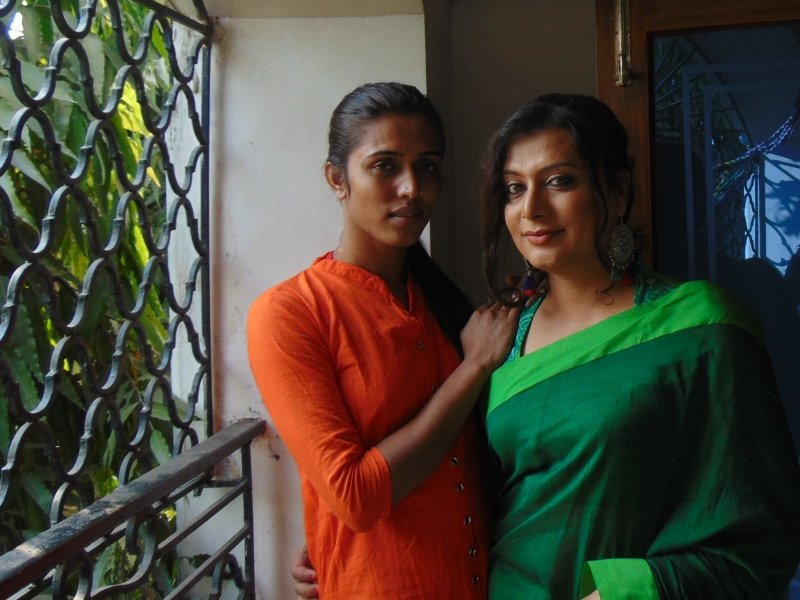 This is a day time photograph of trans activist and first-time actor Sudeb and make-up artist Abir, who is also a trans woman. Both are part of the team of 'Goodbye Beautiful' short film, the subject matter of the accompanying article. They are standing close together in a friendly embrace on a balcony at the film shooting location. Abir's right hand is on Sudeb's right shoulder, while Sudeb's right hand is placed around Abir's waist. They are more or less the same height. Both are smiling slightly as they look on at the camera. To their right is the balcony railing with a tree visible outside. To their left and behind them is a glass panelled door that opens on to the balcony. Photo credit: Pawan Dhall