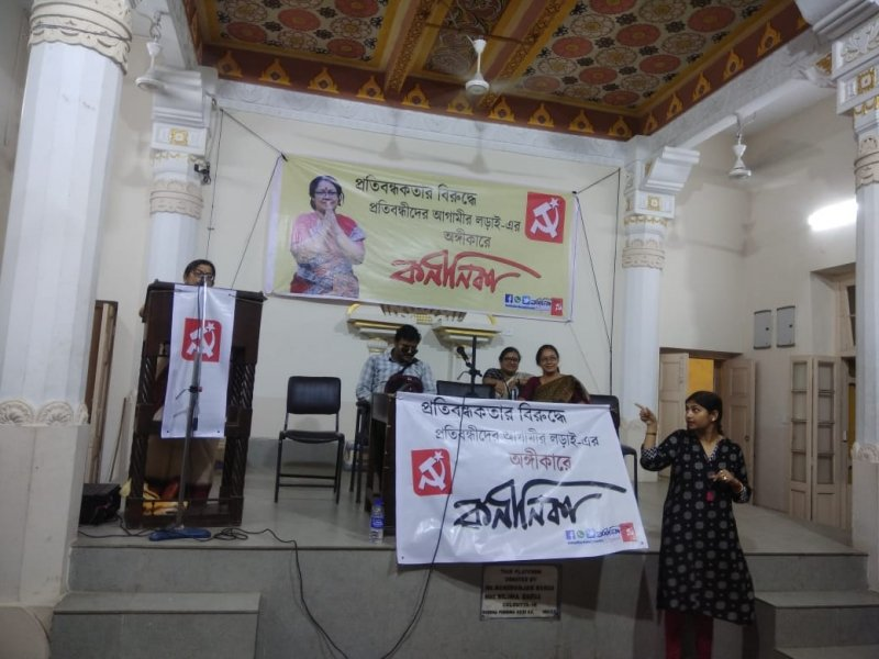 This photograph shows another scene from the disability rights interaction organized by the CPI(M) in Kolkata on May 5, 2019. To the left of the photograph is disability rights activist Shampa Sengupta making a speech on the podium, while sign language interpreter Rajani Banerjee can be seen to the right of the photograph, standing below the podium and interpreting Shampa Sengupta's speech. On the podium are the other speakers – National Platform for the Rights of the Disabled Executive Committee member Anirban Mukherjee, Professor Ishita Mukhopadhyay, and Professor Nandini Mukherjee of the CPI(M). In the background, on the wall behind the podium, is a huge banner that shows a smiling Kaninika Bose Ghosh with folded hands, CPI(M) candidate for the Kolkata Uttar Lok Sabha seat. Next to her photograph is text in Bengali that displays her name in bold letters and talks about her party's commitment to the cause of persons with disabilities. On the top right corner of the banner is the CPI(M) logo, and on the bottom right corner are the party's social media handles. A similar banner is hung in front of a table on the podium behind which the speakers are seated. Tall and semi-ornate white pillars, one each on the four corners of the podium, present an attractive picture, as does the tapestry on the high ceiling of the hall and French windows behind the podium to its right. Photo credit: Rith Das