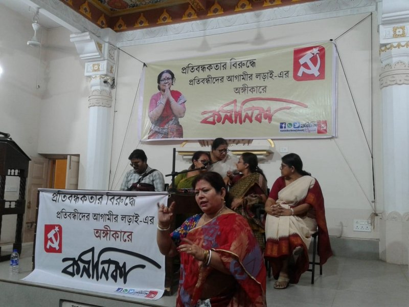 This photograph is similar to the previous one – another scene from the disability rights interaction organized by the CPI(M) in Kolkata on May 5, 2019. Sign language interpreter Nabanita can be seen right in the forefront, explaining a point to the audience, but the speaker who she is interpreting is not the picture. Behind her on the podium are the main speakers of the occasion – National Platform for the Rights of the Disabled Executive Committee member Anirban Mukherjee is first from left; Professor Ishita Mukhopadhyay is talking with the CPI(M) Lok Sabha polls candidates Kaninika Bose Ghosh and Professor Nandini Mukherjee; while disability rights activist Shampa Sengupta looks on. Behind the podium is a banner that presents a smiling Kaninika Bose Ghosh with folded hands, as the CPI(M) candidate for the Kolkata Uttar Lok Sabha seat. Next to her photograph is text in Bengali that displays her name and talks about her party's commitment to the cause of persons with disabilities. A similar banner is hung in front of a table on the podium behind which the speakers are seated. Photo credit: Rith Das