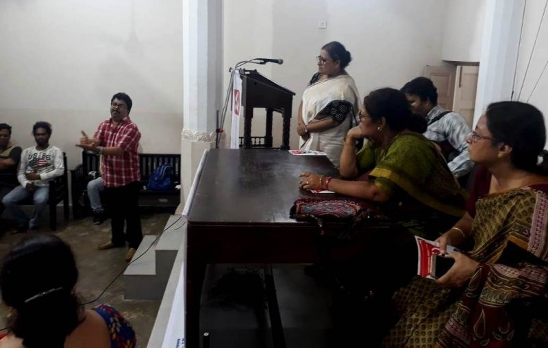 This photograph shows a scene from the disability rights interaction organized by the CPI(M) at Maha Bodhi Society Hall in Central Kolkata on May 5, 2019. The objective was to convey what the CPI(M) manifesto for the 2019 Lok Sabha polls had to say about the concerns of persons with disabilities. To the right of the photograph is a podium where a number of speakers are either standing or seated behind a table. These include Professor Ishita Mukhopadhyay (standing and furthest away), faculty at the University of Calcutta; Anirban Mukherjee, Executive Committee member of the National Platform for the Rights of the Disabled and CPI(M) member; Kaninika Bose Ghosh, Kolkata Uttar Lok Sabha election candidate; and Professor Nandini Mukherjee, Kolkata Dakshin Lok Sabha election candidate (closest to the camera). To the left, next to a few steps leading up to the podium, is Sumanta Ghosh, a member of a disability rights network in Kolkata. He is making a point during the interaction using sign language, as a few members in the audience seated behind him look on. A sign language interpreter can be seen in the forefront with her back to the camera. In the background, tall pillars of the high-ceilinged Maha Bodhi Society Hall seem to make a mark against creamy white walls. Photo credit: Rith Das