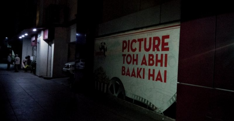 "This long shot photograph has a symbolic association with the accompanying article. It shows a large banner pasted on a wall outside a cinema hall somewhere in an Indian city. The text of the banner consists of Hindi words written in English alphabets – it says in large red letters against a white background: ""Picture toh abhi baaki hai"". A literal translation would be that the film is yet to be over, while a deeper meaning would be that there is a twist in the story and more is yet to happen. In the context of the article, which is about the 2019 Lok Sabha poll results and the strategic role that civil society stakeholders need to play in India today, the banner text means that one should not give up hope and persevere – all is not lost. A short distance away from the banner some people can be seen standing around a ticket counter. The photograph is a night time one, taken using the light from the lamps outside the cinema hall, including those outside the ticket counter. Photo credit: Pawan Dhall."
