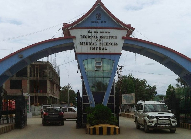 The photograph shows the main entrance to the campus of the Regional Institute of Medical Sciences (RIMS), Imphal. This institute is not only one of the key government hospital cum medical colleges in Manipur, its psychiatry department is also considered to be one of the few queer-friendly options in the state in terms of mental health services. The photograph is a day-time picture and it shows the imposing entrance stand out against a cloudy sky. The entrance consists of a central column with a pagoda like rooftop, with an arch on either side of the column sloping down to the ground. There are iron gates on either side of the column through which vehicles can be seen moving in and out. The background consists of a building under construction and several trees inside the RIMS campus. Photo credit: Bonita Pebam