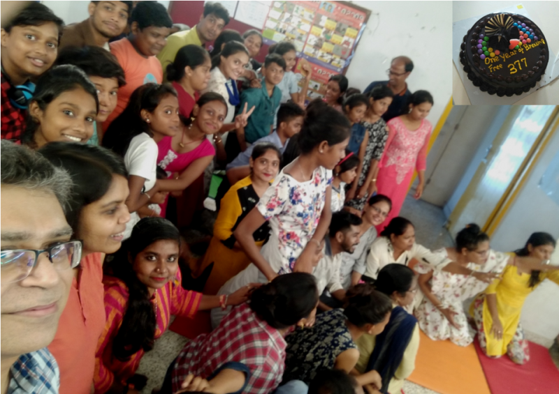 "This photograph is a selfie shot taken by the author at an event organized by NGOs SAATHII and Thoughtshop Foundation to mark the first anniversary of the Supreme Court's verdict on Section 377, Indian Penal Code. The event was organized at Thoughtshop Foundation's meeting space in Kolkata on September 6, 2019, exactly one year since the verdict. The participants included around 50 individuals associated with the youth groups that Thoughtshop Foundation works with. Staff members of the two NGOs were also present. A diversity of genders and sexualities was represented at the gathering. The author shot the photograph with the phone in his right hand. A part of his smiling face peers and looks up into the camera, with around 30 other participants to his left, some seated and others on their feet. While half of them are smiling at the camera, flashing victory signs, the other half are smiling and waving excitedly at another photographer, who is not visible in the photograph. Overall, it is a photograph with much happening and with everyone in a celebratory mood. The top right hand corner of the photograph has a small inset photo of a large chocolate cake that was cut on the occasion. The icing on the cake says ""One year of breaking free 377"". Photo credit: Pawan Dhall"""