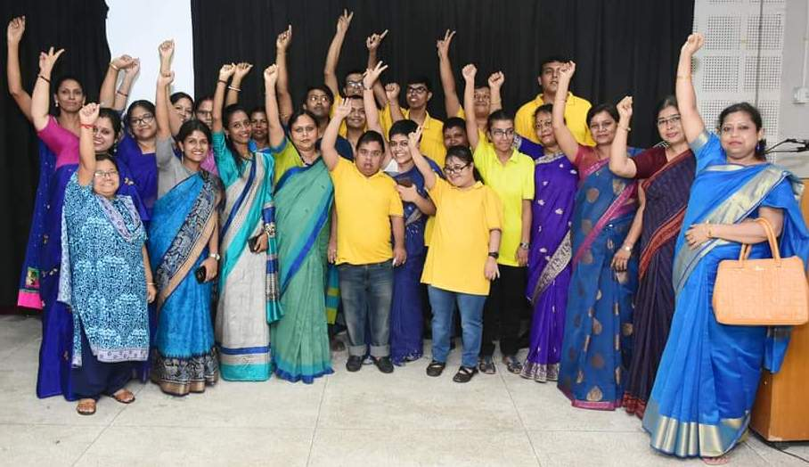 This photograph shows the Sip N Bite team members along with their parents (mothers), mentors and well-wishers. There are about 25 individuals standing together for a group photograph on a stage. People are smiling cheerfully at the camera and most of them have their right hand raised in a victory sign. The core Sip N Bite team is in the centre, many members in bright yellow t-shirts. They are flanked on the two sides by the others. Photo courtesy Transcendent Knowledge Society