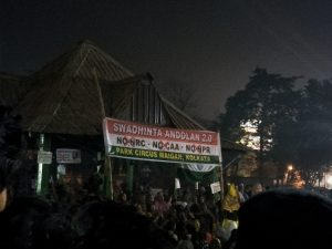 "This is a night time shot of a public protest being staged at the Park Circus Maidan in South Kolkata against the Citizenship (Amendment) Act, 2019, National Population Register and National Register of Citizens in India. A long shot from behind a few bystanders shows a large crowd gathered in and around a gazebo near the main entrance to the Maidan. The protestors are almost all women. A huge banner strung on two bamboo poles placed amid the crowd says in bold text: ""Swadhinta Andolan 2.0 – No NRC, No CAA, No NPR – Park Circus Maidan, Kolkata"". The backdrop to the text is made up of the national flag colours and pattern. The words 'NPR', 'NRC' and 'CAA' are crossed out. Other smaller banners with similar wording can also be seen. In the background are tall trees, which, along with the gazebo rooftop, stand out against the dark sky. Incidentally, the gazebo in question was the starting point of 'Friendship Walk '99', which was held on July 2, 1999 and which many believe to be the first ever rainbow pride walk in India and South Asia. Photo credit: Pawan Dhall"