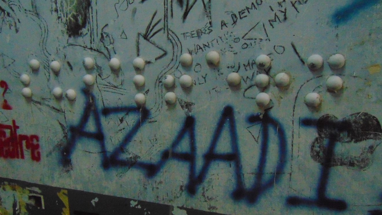 This photograph shows a daytime close shot of one of the Braille graffiti on display near a staircase at the English departmental building at Jadavpur University, Kolkata. The graffiti has been created out of white table tennis balls cut in halves and then screwed onto the wall using cement to form the English Braille letters for the word 'subaltern'. Since this is a close-up shot, the graffiti spans across the photograph. But the wall on which the graffiti has been created is replete with other graffiti as well bits and pieces of which are visible in the photograph. Right below the Braille graffiti, the word 'azaadi' has been spray painted in blue on the wall in large-sized capital letters in English. Photo credit: Pawan Dhall