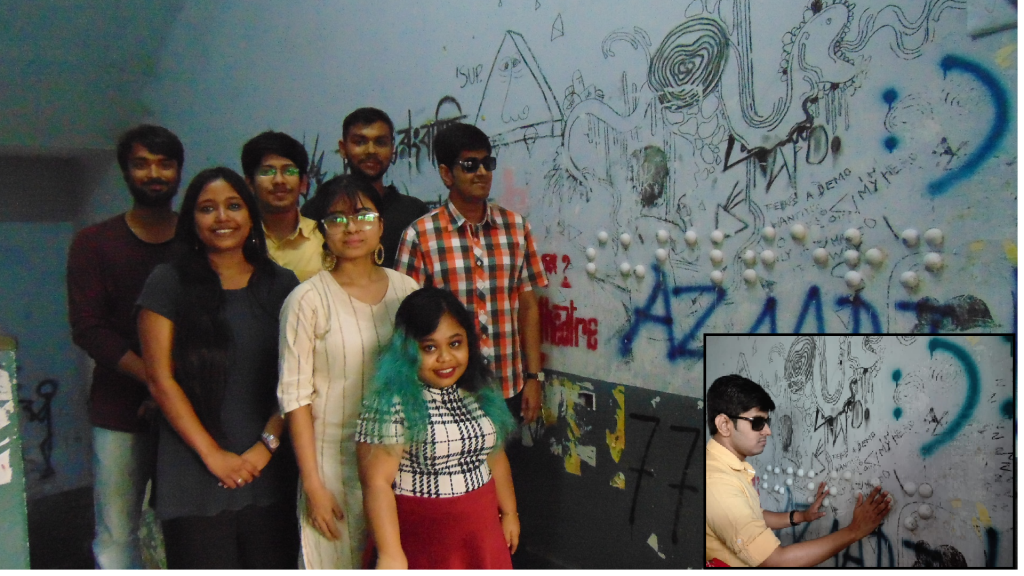 "This photograph shows the entire team that was behind the creation of the Braille graffiti at Jadavpur University. The team is standing in a close group, roughly in three rows, with the graffiti ""Subaltern"" written on a wall to their left. The wall is replete with other colourful graffiti as well. The team members are all smiles as they pose for the camera. In the last row, from left to right are Emon Bhattacharya, Subhradeep Chatterjee and Anik Mandal; in the central row are Manikankana Sengupta, Utsa Ghosh and Professor Ishan Chakraborty; right in front is Chandrima Mukhopadhyay. To the bottom right of the photograph is an inset of Professor Ishan Chakraborty reading the Braille graffiti with his fingertips. Photo credits: Pawan Dhall, Subhradeep Chatterjee (inset)"