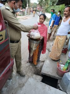 This daytime photograph shows a police officer in khaki uniform and wearing a mask handing over a packet of food items to a woman in Sonarpur, South 24 Parganas district of West Bengal. A few other individuals standing around look on. The locality seen in the photograph seems to be part of a semi-urban area. The photograph was shot on April 2, 2020. Photo credit: Anonymous