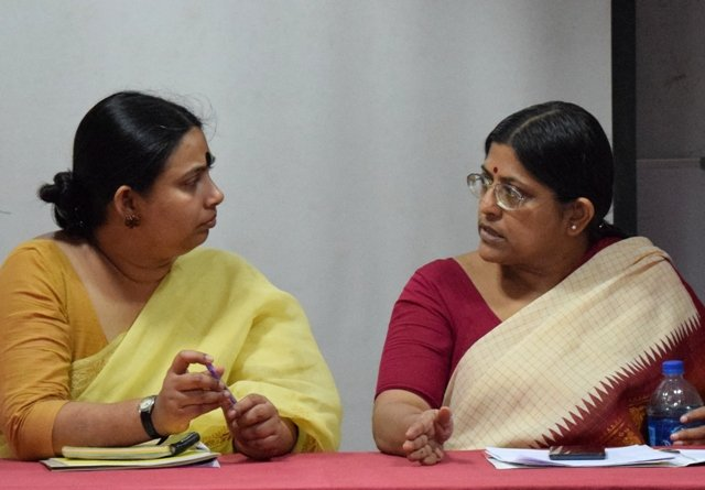 This photograph is a close shot of the two speakers of the meeting – Dr. Rukmini Sen (Assistant Professor, Ambedkar University Delhi) and Shampa Sengupta (founder of Sruti Disability Rights Centre) – seated behind a long table meant for presenters. They are looking at each other and conversing. Dr. Rukmini Sen is holding on to a pen, while Shampa Sengupta has a bottle of water in her left hand. A few documents and other personal items are placed on the table before them. Photo credit: Abhirupa Kar