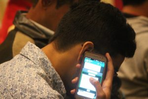This photograph is a close-up side shot of a participant with a certain degree of blindness at the Inclov meet-up on January 21, 2018. The participant, a young man, is listening into his mobile phone. He is leaning forward a bit, the side of his face hidden by his hand and phone – only his hair, neck, ear, prettily printed shirt, and spectacles are partially visible. The screen side of the phone is turned towards the camera and is brightly lit with text windows. In the background the blur of a few other participants can be seen. Photo credit: Prosenjit Pal