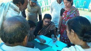 This is daytime photograph that shows Joyita Mondal participating in a health camp for the general public somewhere in the Uttar Dinajpur district of West Bengal. She is seated at a table in a grassy open area carrying out what looks like paperwork for client registration. A number of men and women, of different age groups, and a child can be seen standing patiently around the table, looking at what she is writing. The child is peering closely at her work. All the people waiting seem to be part of the urban and rural poor. In the background, an arrangement of plastic chairs seems to ring the open area where Joyita Mondal is seated. Photo courtesy Joyita Mondal