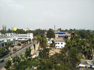 This is a daytime long shot of a part of Islampur town taken from the third or fourth floor of a building. To the left of the photograph is a bus terminus with a few vehicles parked. The terminus does not seem to have much of a crowd. Next to the terminus is a near empty road, and to the right of the road is an expanse showing several low rise buildings, and numerous palm trees and other vegetation. The background consists of a lightly clouded grey-blue sky. Photo credit: Pawan Dhall