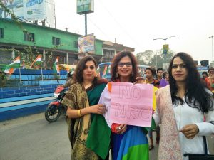 "This photograph shows an early evening scene from the first rainbow pride walk organized in Gangarampur town in Dakshin Dinajpur district of West Bengal on January 10, 2020. The pride walk was organized on the occasion of Dinajpur Natun Aalo Society, an NGO led by trans activist Joyita Mondal, completing 10 years of its functioning. The photograph shows a smiling and bespectacled Joyita Mondal holding up a small banner that says ""No NRC"". She is flanked on either side by trans women, one on each side – the three of them dressed elegantly and in attractive colours. Behind them more of the pride walk participants can be seen. The background shows some road traffic; buildings, hoardings and trees along the road; and a series of flags of a particular political party fitted along the road divider. Photo credit: Pawan Dhall"