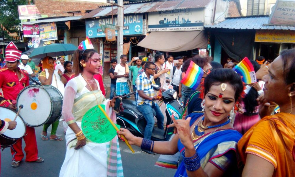 This daytime photograph shows a scene from the first rainbow pride walk organized by Dinajpur Natun Aalo Society in Islampur in 2017. The event was titled 'Sathiya Uttorer Gourab Jatra'. The photograph shows a number of walk participants, mostly trans women, passing through a busy street in Islampur. Some of the participants are dressed in colourful attire and dancing to the music of drummers. Others are waving small rainbow flags. A couple of two-wheelers are moving along with the walkers. A crowd of bystanders can be seen on the pavement which is lined with a variety of shops. Some people are using their mobile phones to take photographs or videos of the walk. All in all a cheerful and dramatic capture of the walk. Photo courtesy Dinajpur Natun Aalo Society