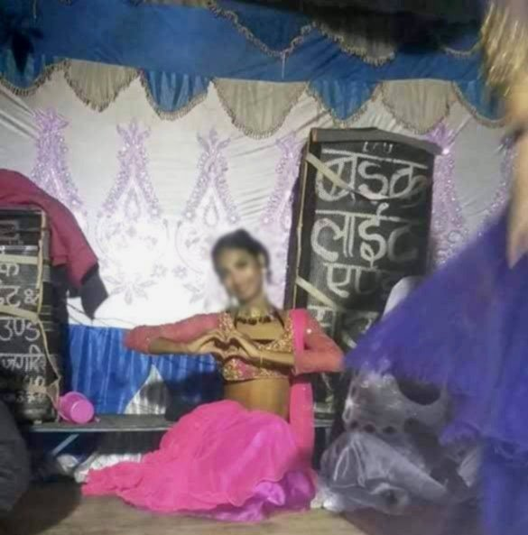 The photograph shows a young Launda dancer from West Bengal posing for the camera somewhere in Bihar before a performance. She is seated in a graceful pose on a wooden stage, dressed in a bright mauve 'ghagra-choli', and smiling at the camera while forming a love sign with her hands. Her face has been blurred to maintain confidentiality. The stage is well lit and has a decorative covering. Sound and light equipment for the stage can be seen piled up behind the dancer. Another dancer can be seen twirling on the stage – only partially visible to the right side of the photograph. Photo courtesy Joyita Mondal