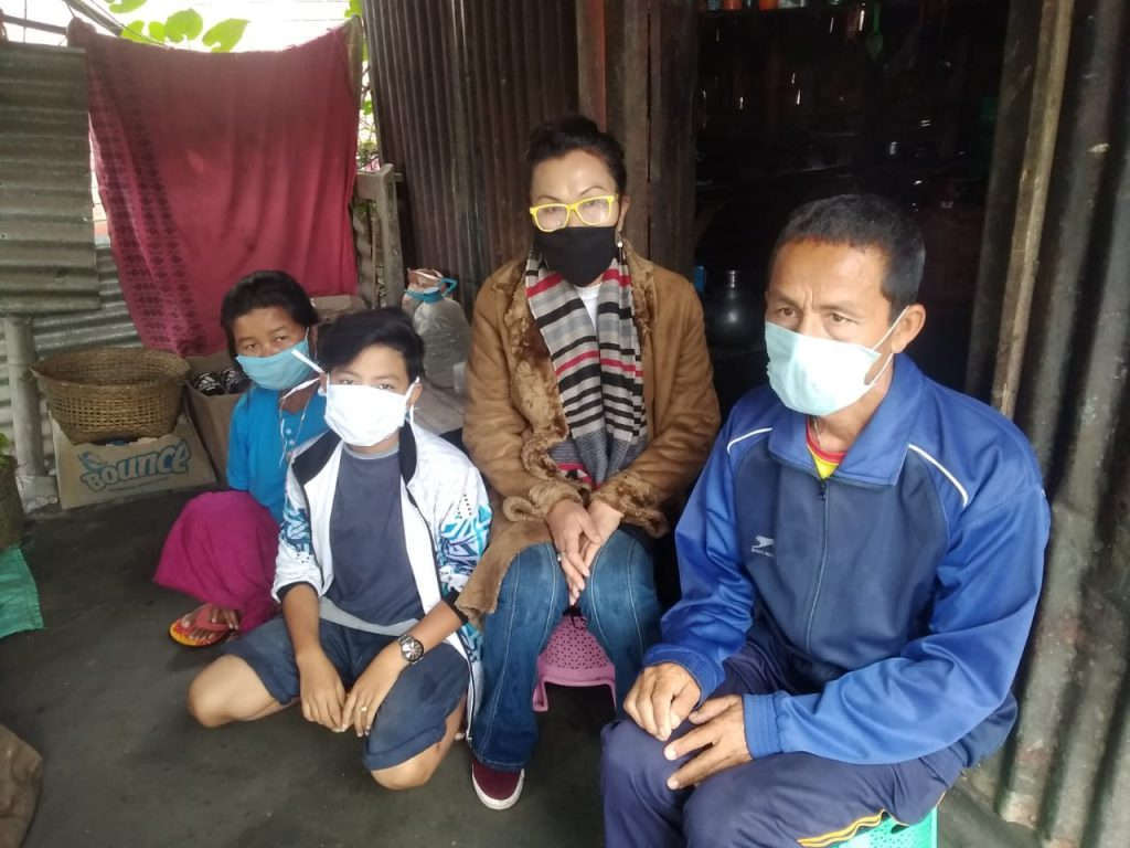 This daytime photograph shows Atey with the author and his parents at his home. All four individuals are wearing masks meant to prevent coronavirus transmission. Atey is semi-kneeling on the floor, while his mother (to his right), the author (to his left) and his father (next to the author) are seated on low plastic stools. The room in which they are seated shows a humble home environment – it has asbestos walls, a window space screened by a large piece of cloth and some household items like a cane basket and plastic water containers. A part of an adjoining room, possibly the kitchen, can be seen behind the author, but it is in darkness. Photo credit: Borish Yumnam