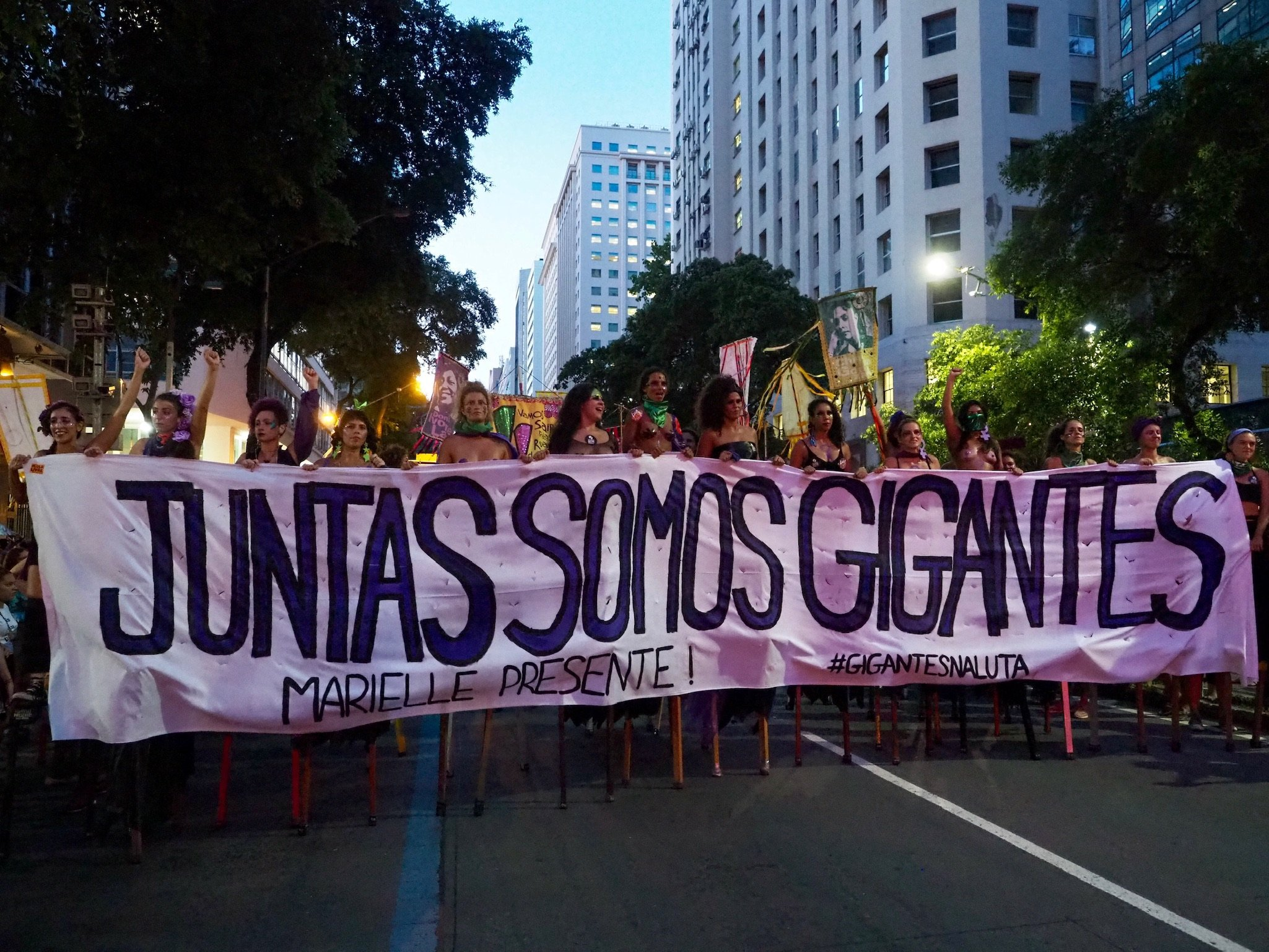 "This photograph shows an outdoor scene from the shooting of the film 'Marielle's Legacy Will Not Die'. Around 14-15 cis and trans women can be seen walking on tall stilts in a single row on a street of a Brazilian city. The row of women stretches across the street and the marchers are holding a huge cloth banner that says in large Portuguese lettering ""Juntas somos gigantes"". In English this translates to 'together we are giants'. Below the main banner text is smaller text that says ""Marielle presente!"" and ""#gigantesnaluta"". All the text on the banner is in bold capital letters. The banner runs across the row of women and covers them such that only their necks and faces are visible above the banner and the stilts below. A crowd of people can be seen behind the women carrying more posters and banners. In the background are trees lining the street and tall buildings against an early evening blue sky. Photo credit: Pilar Rodriguez"