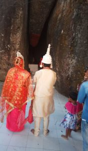 This daytime photograph shows Raj and Meena at their wedding ceremony at Hatisila Ganesh Temple on the outskirts of Guwahati. The photograph has been taken from behind the couple and their faces are not visible. Raj and Meena are in customary wedding attire and standing with folded hands, facing the temple deity but a little outside the temple. The temple is a natural and mammoth rock shape on a hillock. Part of the rock shape resembles an elephant's trunk, hence the name of the temple. The deity is placed in a cave-like space between two large rocks – the space looks like an elephant's mouth. A young girl is standing with folded hands close to the deity. The couple are some distance away from the deity. A few people, including another girl child, are standing next to the couple. The temple floor, both inside the cave-like space and outside, is made up of white tiles. The author Shivalal Gautam was present to provide moral support to the couple and shot the photograph.