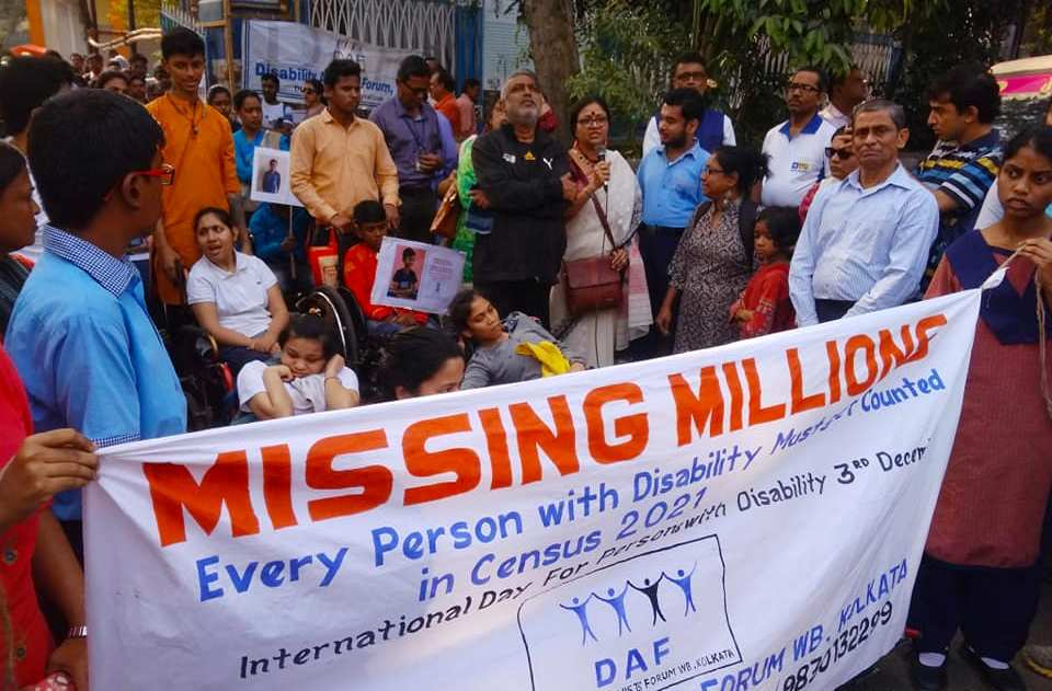 "This daytime photograph shows a scene from a rally held in Kolkata on the International Day of Persons with Disabilities, December 3, 2019. Scores of people carrying placards and posters have gathered at the starting point of the rally. The participants are a mix of age groups, genders and disabilities, among them a number of young people in wheelchairs. One of the participants is speaking into a microphone, while the others look on. Right at the forefront are some people carrying a large banner which is headlined 'Missing Millions'. Below the headline is text that says: ""Every person with disability must get counted in Census 2021 – International Day for Persons with Disability 3rd December"". Below the text is the logo of the Disability Activists Forum WB, Kolkata, and a part of their contact information is visible below the logo. The full contact details are: ""98302 62165 / 98315 87378 / 98301 32299; disabilityactivistsforumwb@gmail.com"". The photograph is representative in nature in relation to the accompanying article. Photo courtesy Disability Activists Forum WB, Kolkata"