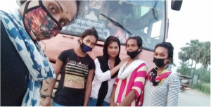 This daytime photograph shows five trans women, all Launda dancers, posing for a selfie photograph on their way back to West Bengal from Bihar. They are standing on the side of a road. The individual who shot the photograph can be seen up close – their masked face peering into the camera and part of the body making up the left side of the photograph. Behind them are four other individuals, only two of them masked properly. They all seem to be in their late teens or early 20s. They seem to be exhausted with their journey. Behind them can be seen the front side of a bus, probably the one in which they were travelling. The front window pane of the bus makes up most of the background. To the right side of the photograph is the road – a two wheeler can be seen whizzing past. Tall palm trees and other vegetation can be seen on the far side of the road. Photo courtesy Joyita Mondal