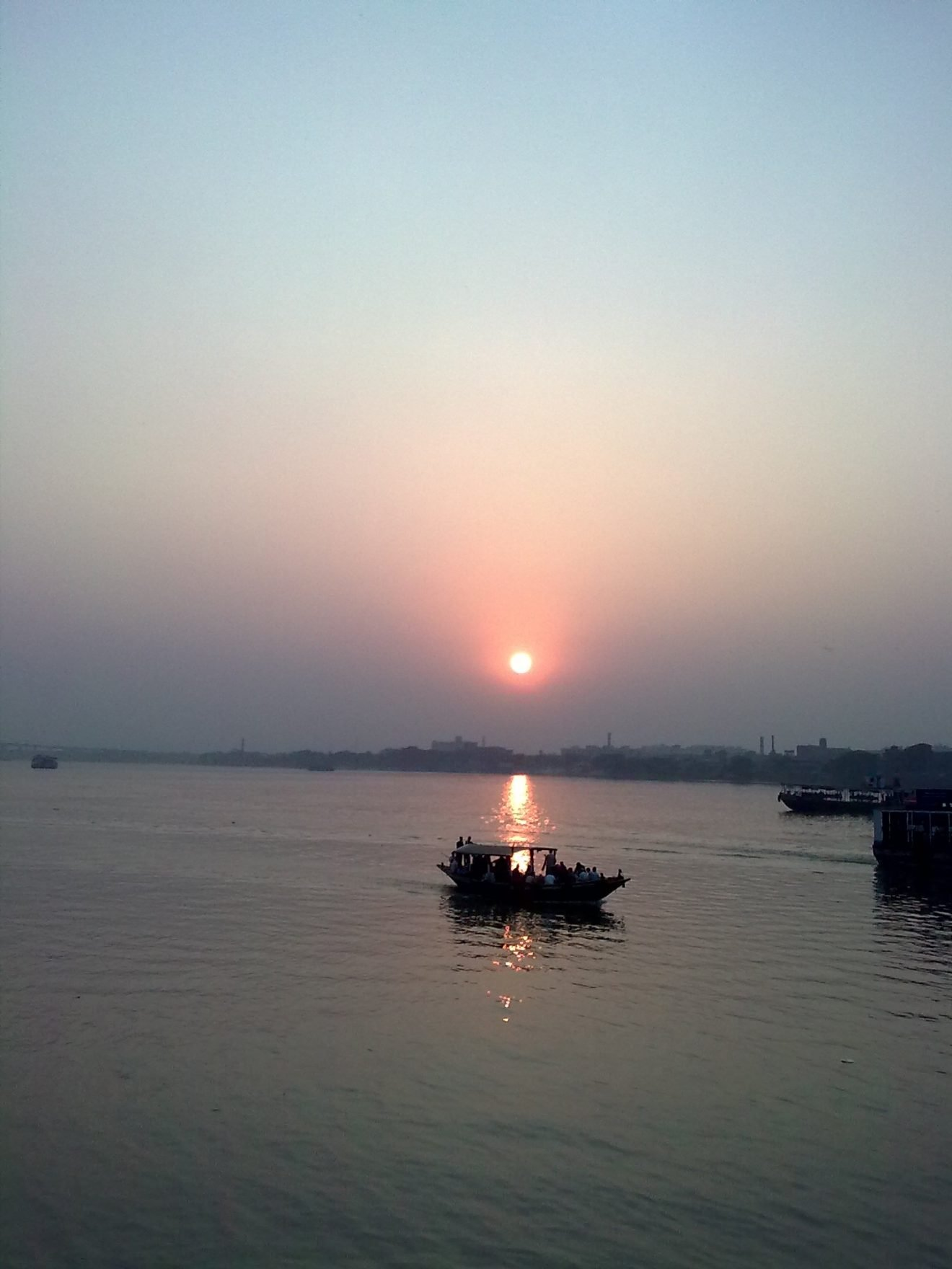 This photograph is an evening-time long shot of the Hooghly River from the river bank on the Kolkata side. The photograph shows a large expanse of the river. The backdrop shows a golden yellow setting sun and a blue sky tinged with orange light in the horizon. The river waters seem absolutely calm and a large passenger boat with many people on board can be seen right in the line of the sun's reflection on the water. More vessels can be seen towards the right edge of the photograph and in the distant background. The river bank on the far side is a hazy line of trees and a few industrial structures. The overall sense is one of serenity. The setting sun can be a symbol of renewal as much as a rising one. Photo credit: Pawan Dhall