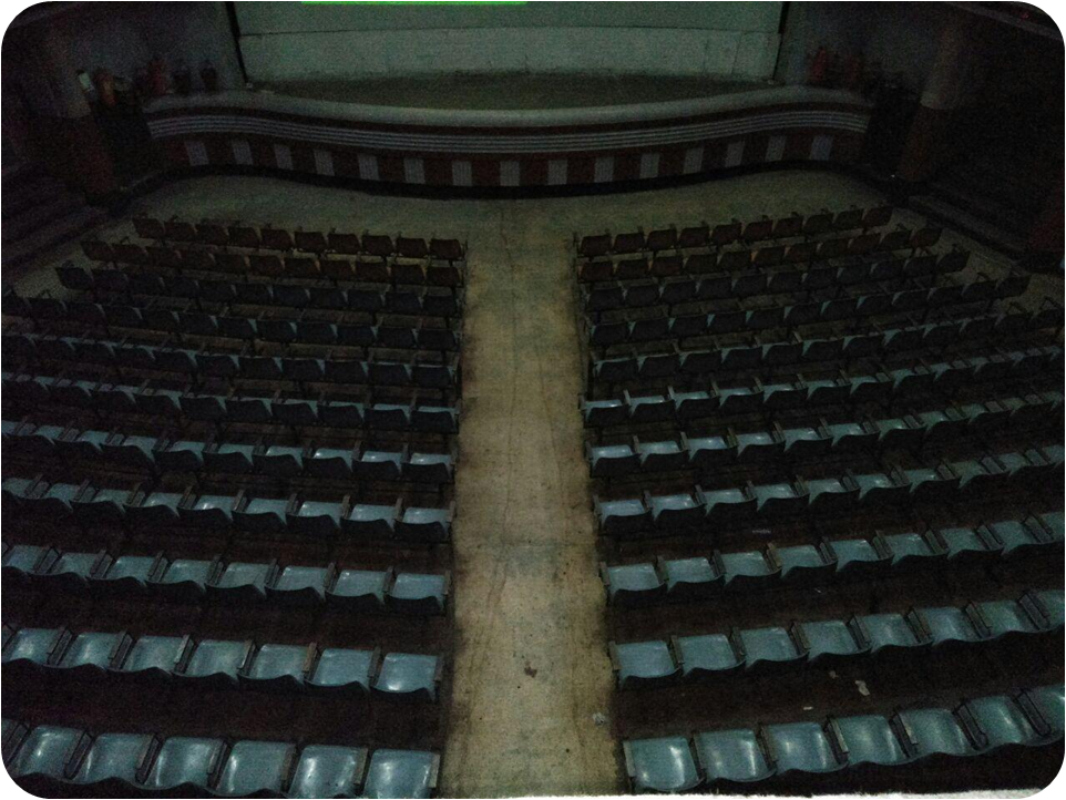 This is a photograph taken in dim fluorescent light from the balcony section of the Basusree cinema hall in South Kolkata. Basusree cinema is an important symbol of nostalgia and cultural history for the city of Kolkata. The photograph shows several rows of seats on the ground floor section of the hall, an aisle running through the centre of the hall, a passage between the front row and a stage, the stage itself on the far end, and a small lower portion of the screen on the stage. A few steps leading to the exits can be seen on either side of the stage, as also fire fighting equipment kept on both ends of the stage. The rows of seats are all empty, there is no film being screened, and no one at all can be seen in the entire expanse of the hall. The photograph has rounded corners. A white background behind the corners seems to give the feel that the photograph is held in place by photo corners in an old-style album. Photo credit: Pawan Dhall