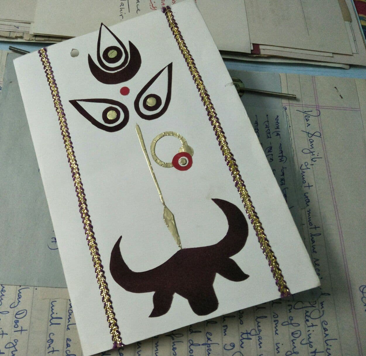 This main illustration is a photograph of the front cover of a Durga Puja greeting card received by queer support group Counsel Club, Kolkata in October 1998. This handmade card is vertically oriented and has cut-outs made out of thick gold, brown and red coloured paper pasted on white chart paper. The cut-outs depict the three eyes of Goddess Durga, a red 'bindi' on her forehead, a nose ringlet, and the nose itself in the form of a long spear pointing downwards towards the head of a buffalo, symbolizing the 'rakshasa' the goddess is supposed to slay. The goddess' eyes look striking, and given that her mouth has not been shown with any cut-out, it almost appears as if she is wearing a mask. The artwork is framed on either side by two long strips of 'zari' work. The card is placed on an open file of letters received by Counsel Club. A few letters can be seen filed in the background, but the contents are not quite legible. Photo credit: Pawan Dhall