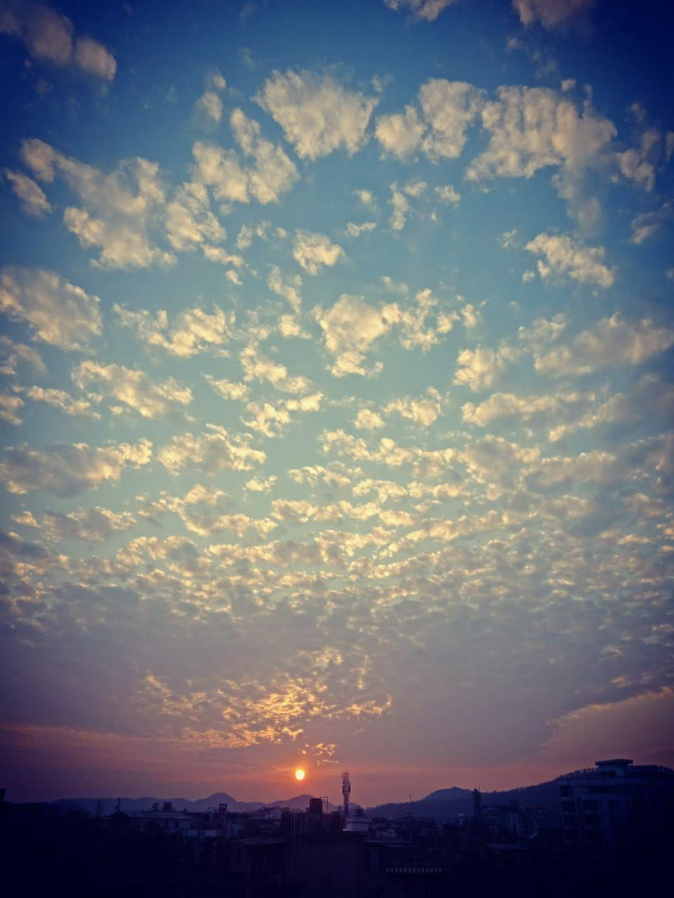 This photograph is a striking long shot of the early morning sky taken from the balcony in Mayuri's home. A major part of this vertical oriented photograph consists of silver-white clouds flecking a blue sky like a carpet right up to the horizon, where a rising sun has painted the sky in hues of orange and pink. A few buildings and trees can be seen in the near distance, somewhat still in the dark, with a number of hills rising behind them in the far distance. The entire scene is one of morning calm symbolizing peace and positivity. Photo credit: Mayuri