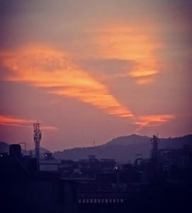 This photograph is another long shot taken from Mayuri's balcony, this time of a breathtaking sunset. In the foreground are a number of buildings and a couple of mobile phone towers, looking gloomy in the dusk. Behind them graceful hills rise to meet the evening sky, which is where all the drama in the photograph is. Three broad streaks of flaming orange light up a violet-hued gray sky, though the sun itself seems to have set a while ago. The photograph does not show much human activity, other than three small sources of light originating from the buildings. This seems to have added to the quietude of the scene. Photo credit: Mayuri