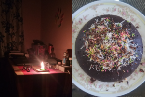 This is a panel of two photographs. On the left is a close shot of Namrata's writing table, lit up only with a candle placed on a coaster. The table is placed in the corner of a room. It is covered with a table cloth which has a pattern of broad checks. An assortment of items crowd the table – a pair of spectacles, laptop computer (not in use), earphones, an electric extension board with a charger fitted into it, a number of books and diaries, a liquor bottle, and what seems like a plastic bottle of hand sanitizer. Despite these and more items, the table has an organized look about it. Some stickers can be seen mounted on the wall behind the table, as well as window curtains to the left of the table. The adjoining photograph on the right shows a dark chocolate cake placed on a plate. The cake surface is almost entirely covered with shavings of chocolate and a number of other condiments. This mouthwatering cake was one of Namrata's culinary experiments during the lockdown. Photo credits: Namrata
