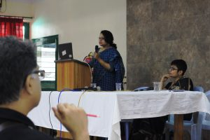 Psychiatrist Dr. Madhurima Ghosh speaks during the first panel on counselling needs of queer individuals and their families. She is seen making her presentation standing at the podium, while operating a laptop and holding a microphone. Seated to her left on a stage meant for the speakers is clinical psychologist Shilpi Banerjee. Two microphones and three glasses of water can be seen on a long table placed in front of Shilpi Banerjee. In the forefront left side of the photograph, the side profile of an audience member can be seen. Photo credit: Kaushik Gupta