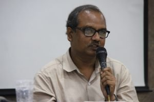 Close up shot of psychiatric social worker Mohit Ranadip as he speaks during the first panel on counselling needs of queer individuals and their families. He holds a microphone in his hand as he speaks. A white screen used for projections can be seen behind him. Photo credit: Kaushik Gupta
