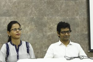 HIV activist Sudha Jha (left in the photograph) and advocate Kaushik Gupta during the post-lunch panel on laws and policies related to mental health. Kaushik Gupta has a gentle smile on his face. Both speakers are seated behind a long table placed on a stage meant for the panel speakers. Photo credit: Jia Mata
