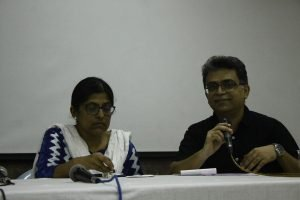 Disability rights activist Shampa Sengupta (left in the photograph) and Varta Trust Founding Trustee and queer activist Pawan Dhall during the post-lunch panel on laws and policies related to mental health. Shampa Sengupta is in a serious mood as she refers to her notes, while Pawan Dhall smiles as he speaks holding on to a microphone. Both are seated behind a long table placed on a stage meant for the panel speakers. Photo credit: Jia Mata