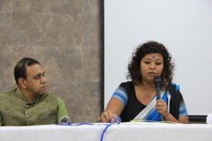 Public health and social justice activist Dr. L. Ramakrishnan (left in the photograph) looks at queer feminist activist Rituparna Bohra as she speaks holding a microphone during the panel on role of educational institutions in safeguarding the mental health of queer students. Both are seated behind a long table placed on a stage meant for the panel speakers. Photo credit: Kaushik Gupta