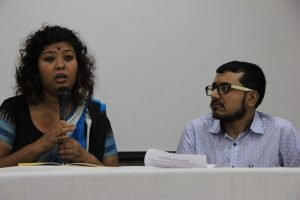 Rituparna Bohra (left in the photograph) speaks during the panel on role of educational institutions in safeguarding the mental health of queer students as gender and sexuality researcher and queer activist Sayan Bhattacharya looks at her and listens to her intently. Both are seated behind a long table placed on a stage meant for the panel speakers. Sayan Bhattacharya has a document related to the symposium placed before him on the table. Photo credit: Kaushik Gupta