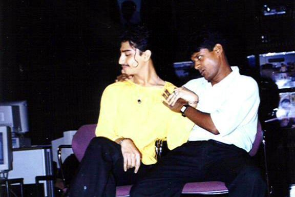 This photograph shows a performance of 'Koti Ki Atma', a comic skit on HIV awareness and gender equity, under way during an HIV awareness event at the Lincoln Room, American Center, Kolkata on June 12, 2001. Two actors facing the camera are seated on chairs placed next to each other on a small stage at the centre of the hall. The spotlight is on the two actors and the background is in darkness. To the left is Anupam Hazra, seated with legs crossed, head slightly bent and turned sideways to their right with eyes closed. A smile is playing on their lips, one hand placed casually across their lap and the other caressing the hand of their companion. Anupam Hazra's companion is Susanta Pramanik who is looking at them ardently, holding on to them in a manner of wooing them, with one hand around their shoulder. Anupam Hazra has a thin long lock of hair curled up sensuously on their left cheek, lending them a delicate look, while Susanta Pramanik appears typically masculine, seated with legs wide open. Anupam Hazra is dressed in a yellow short length 'kurta' and dark trousers; Susanta Pramanik is dressed in a white half shirt and dark trousers, and is wearing a watch. Both actors were also engaged in queer activism and still are. The skit was developed by queer support forums Counsel Club and Integration Society as part of a sexual health project in 2000-01. Photo credit: American Center and courtesy Counsel Club Archives maintained by Varta Trust