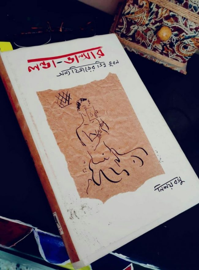 This photograph shows the cover of the book 'Launda Dancer: Anyo Hijrer Bhinna Bhuban'. On a white background, the name of the book is printed on top in a bold red and black typeface, which resembles a casual hand writing style. Below the book title there is a stylized sketch of a Launda dancer putting on make-up in preparation for a dance performance. The sketch lines are in black on a light brown background that looks like paper. The author's name Niloy Basu is printed below the sketch to the right. All the text on the book cover is in Bengali. A yellow sticky note can be seen jutting out of the top of the book on its left side. The photograph shows the book placed on a table with a pair of spectacles and a small Shantiniketan style cloth bag lying next to it. Photo credit: Dr. Kaustav Bakshi