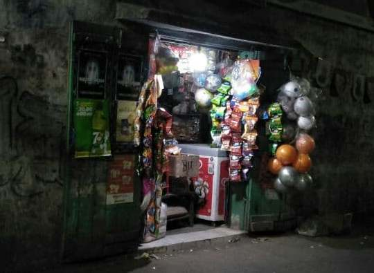 This photograph, a night time shot, shows a brightly lit corner shop in the author's neighbourhood in the Palm Avenue area of Kolkata. There are several colourful packets of food items and sports goods hanging at the shop entrance. More food items, an ice cream refrigerator and other goods can be seen inside the shop. The left side door has several posters of various products pasted on it. The walls around the entrance are full of graffiti. The light from the shop has also lit up the road outside the shop, presenting a cheerful picture amid surrounding darkness. Photo credit: Pawan Dhall