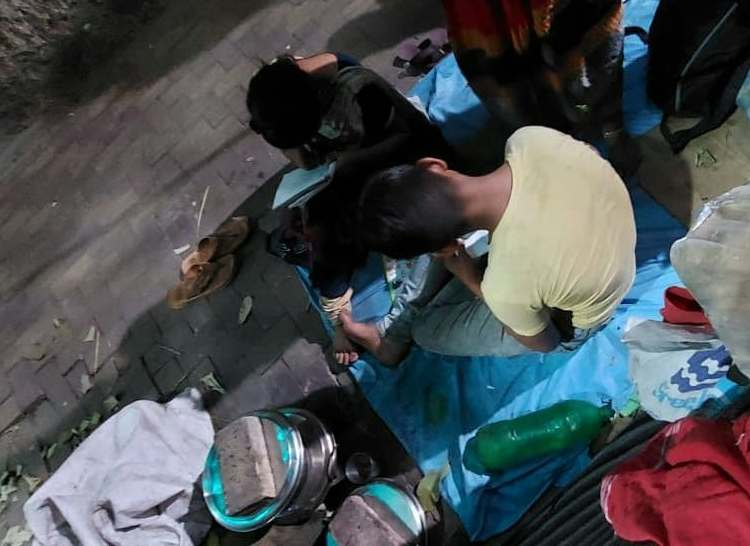 This evening-time photograph shows two children, a girl and a boy, studying on a Kolkata pavement (near the Calcutta School of Tropical Medicine). Both children, no more than 10 years old, are bent over their exercise books, engrossed in writing something. The photographer stood behind them and took the shot from above so that their faces would not be visible (as desired by their mother, who is standing next to them, with only her saree-clad lower legs and feet visible). The children are seated on a tarpaulin spread on about half the width of the pavement. A number of objects can be seen around them – a pair of slippers, some utensils, a plastic water bottle, and some clothes. These indicate that the pavement is also their place of living. The source of light for the photograph is a lamp post to the right of the children and their mother. Their shadows and the light seem to have created an interesting pattern on tarpaulin and the pavement. Photo credit: Sudipa Chakraborty