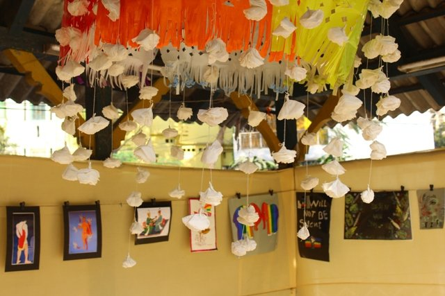 Another decor shot from the 'Kolkata Rainbow Carnival 2018'. In the background is a row of paintings hanging from slender ropes running across two adjacent walls made of fabric. In the forefront is the lower part of a large paper lantern like creation hanging from the roof. The creation has a frilly design made of yellow, orange and white paper, and is fluttering in the breeze. Several white flowers made of 'shola' pith hang from threads attached to the creation – these hanging flowers take up the centre of the photograph and are the focus of the shot. The entire arrangement is housed under a shelter with an asbestos roof supported by wooden pillars and beams. Photo credit: Prosenjit Pal