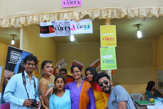 """This last photograph shows part of the Varta team posing outside the Varta stall for a photograph with smiles and pouts. From left to right: Trustee Kaushik Gupta (with a camera in hand), volunteers Sudeb Sadhu, Nikita Kabra and Sudha Jha, a visitor to the stall (name not known), and volunteer Souvik Ghosh. In the background, Founding Trustee and """"Varta"""" Editor Pawan Dhall can be seen raising a cup of coffee as a toast inside the stall. A variety of Varta posters and banners can be seen framing the stall, which is lit up with a fluorescent lamp. A part of the neighbouring stall with a volunteer sitting inside is also visible. Photo credit: Prosenjit Pal"""